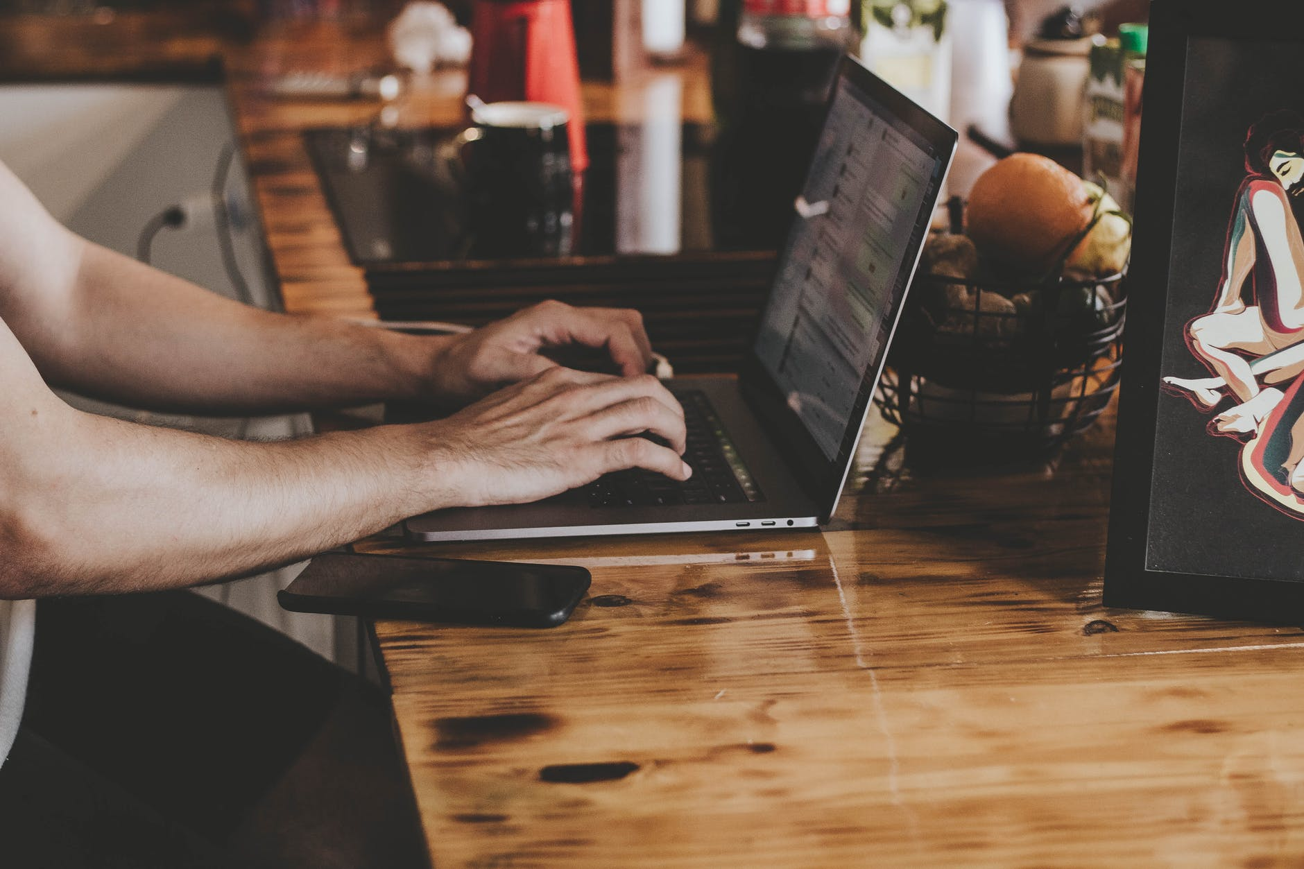 person in front of laptop on brown wooden table